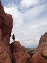 Silhouette of a man standing on a mountain ridge.