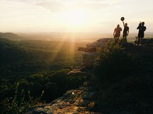 Silhouette of people on top of a cliff overlooking a valley at sunrise.