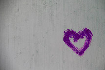 Purple painted heart on a concrete wall
