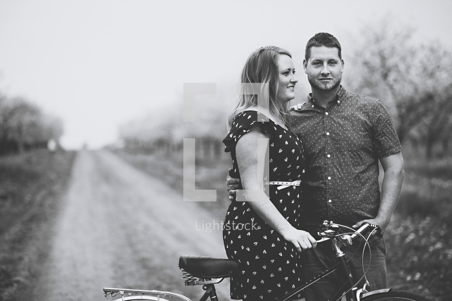 happy couple standing in an orchard with a bicycle