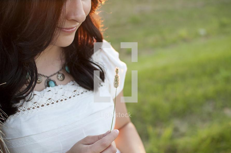 woman holding a piece of a grass