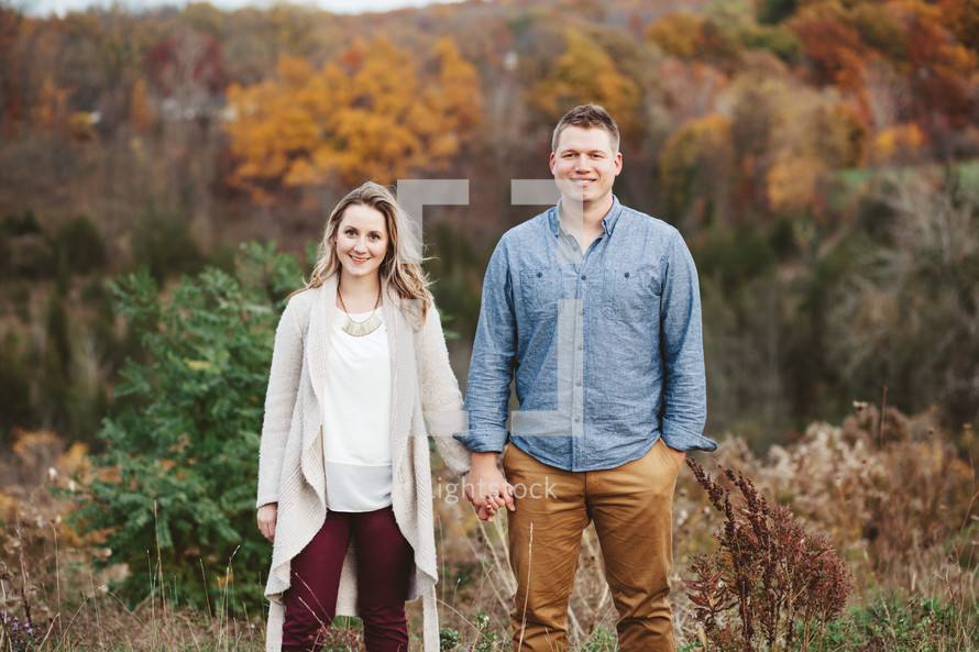couple holding hands outdoors in fall