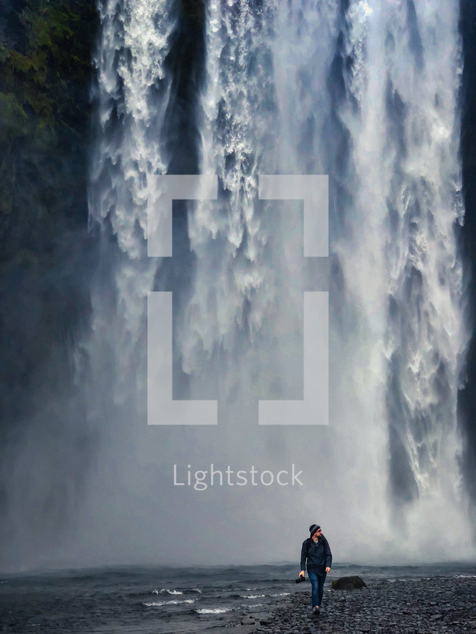 a man walking in front of a waterfall carrying a camera