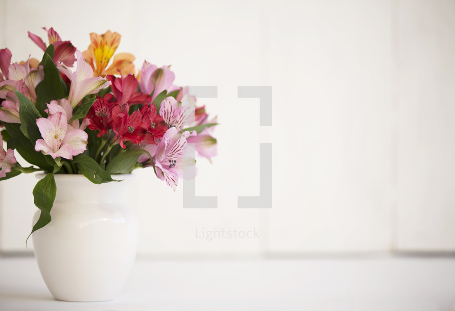 colorful flowers in a vase with a white wood background.