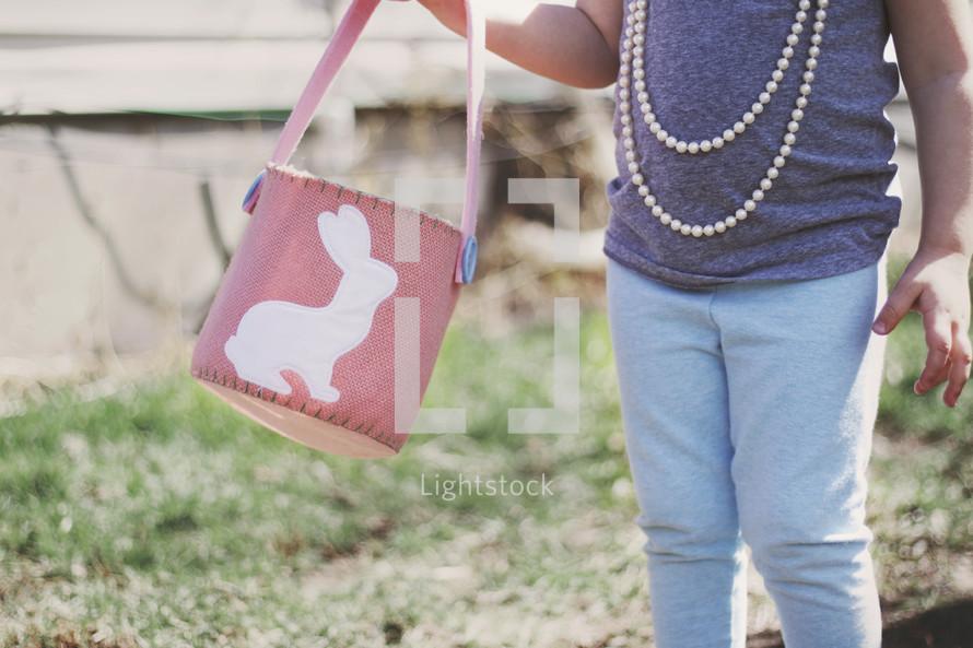 toddler girl holding an Easter basket