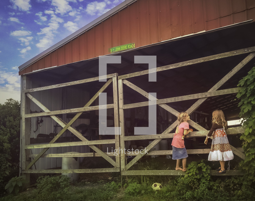 girls standing near a barn