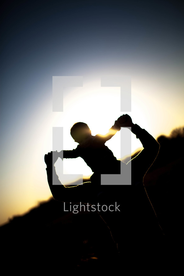 Silhouette of boy riding on man's shoulders at dusk.