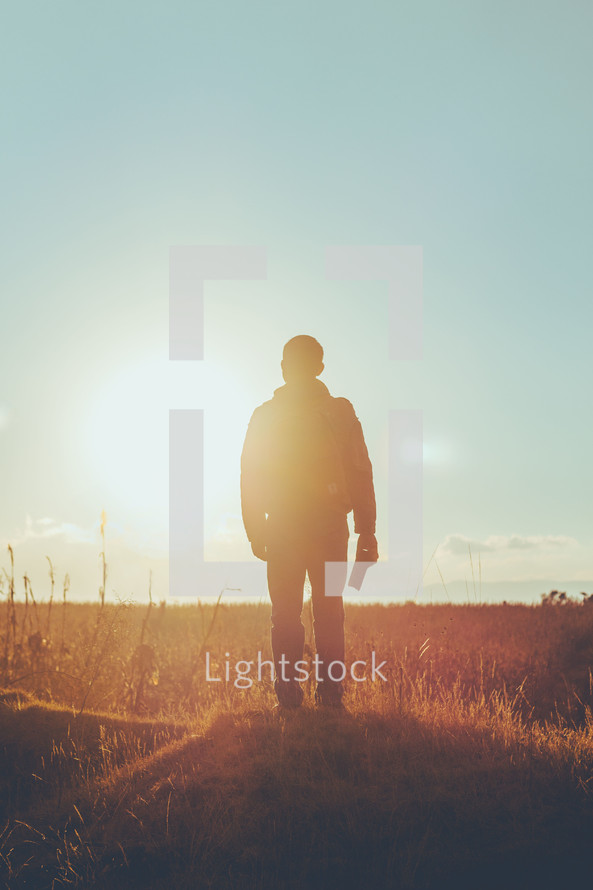 Man standing in sunlight with bible