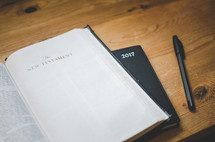 A bible open at the new testaments sits on a 2017 diary on a desk with a pen
