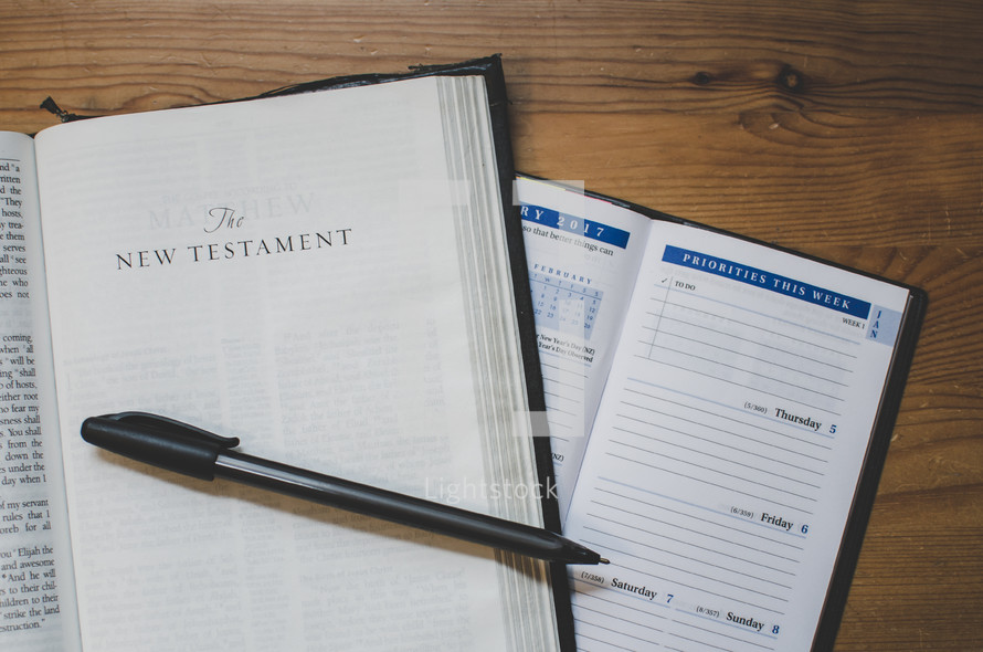 A bible opened at the new testament with a 2017 diary planner open on a desk