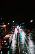 a bus driving on wet roads at night