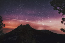 stars in a night sky and silhouette of a mountain peak