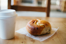 coffee cup and bagel on a napkin