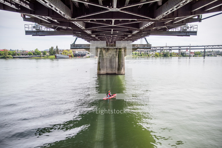 fishing in a canoe under a bridge