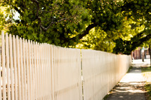 white picket fence and sidewalk in a neighborhood