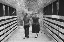 women walking on a wooden footbridge
