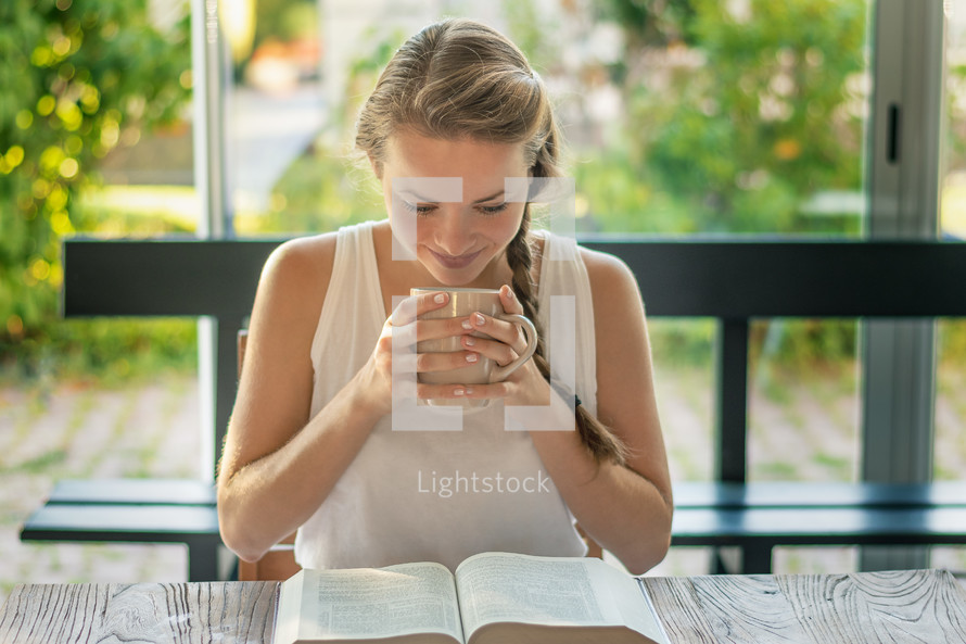 a woman reading a Bible at a table outdoors
