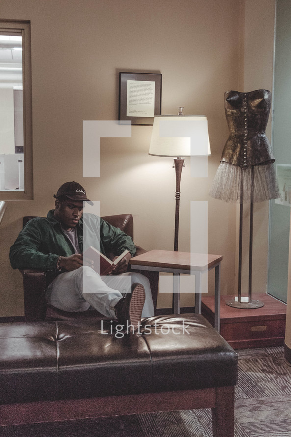 a man reading a book in an armchair