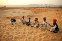 nomads resting in the sand with rifles