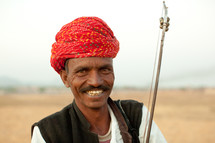 A smiling Indian man in a red turban.