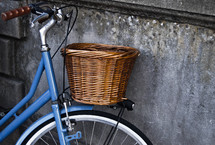 Bicycle with a basket parked against a cement wall.
