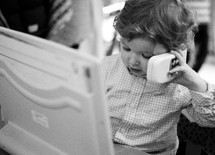 toddler boy on the phone in front of a laptop computer