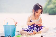 a girl on a beach playing with sand toys