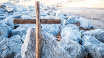 wooden cross on rocks