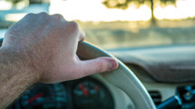 hand on a steering wheel