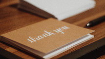 a thank you card on a wooden table