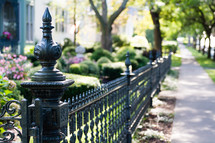 Wrought iron fence along a sidewalk.