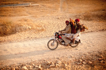 three men on a motorcycle on a dirt road in Pushkar, India