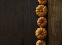 row of orange mini pumpkins on wood