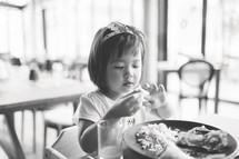 a toddler girl eating food