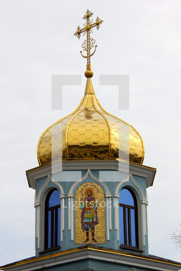 A church steeple with a golden dome and cross.