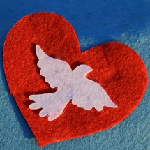 a red felt heart with a white dove