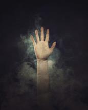 A hand raised through smoke.