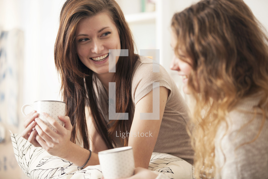 Friends enjoying coffee together while sitting on the sofa.