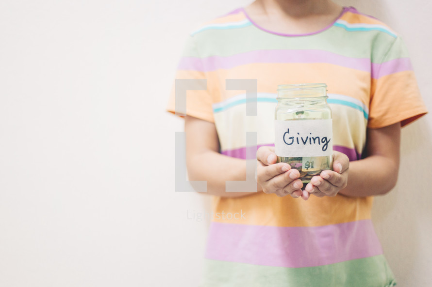 a child holding a giving jar full of money