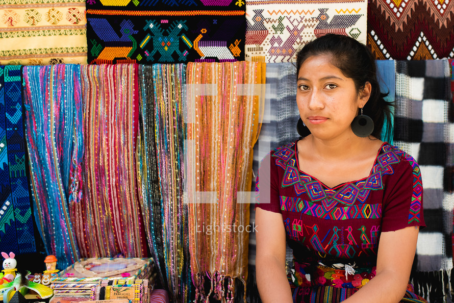 a woman selling blankets in a market
