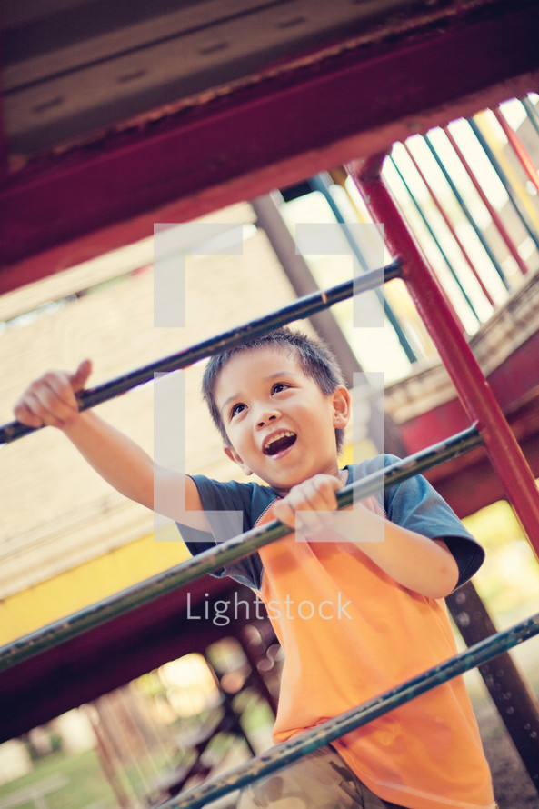 a boy child climbing on a playground