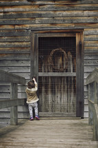 Little girl trying to reach up to open an old wooden door.