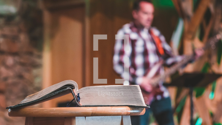 open Bible on a pulpit and worship team playing music