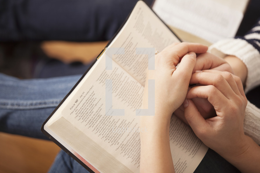 praying hands holding hands over the pages of a Bible.