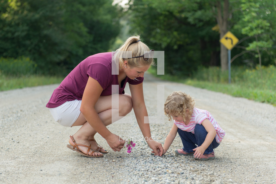 mother and daughter looking for rocks