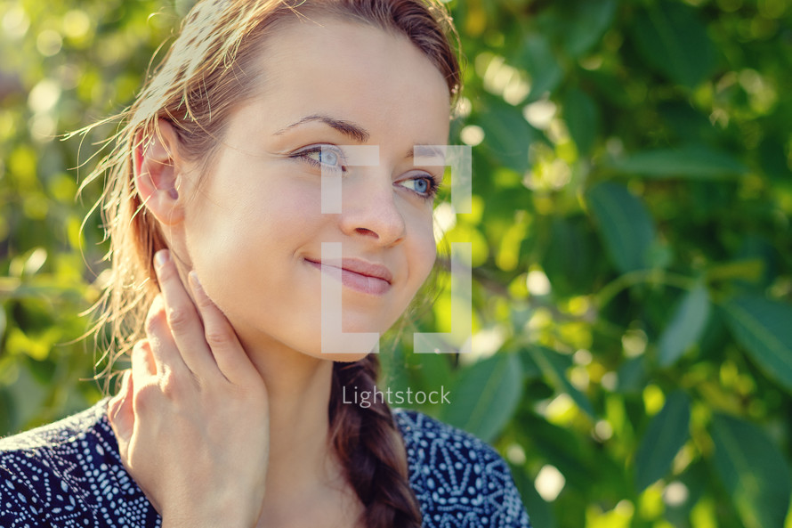 shy smiling young woman in a garden