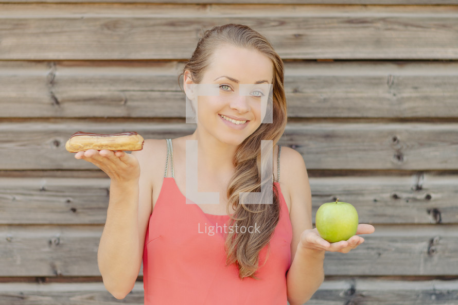a woman holding sweets and an apple