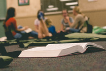 Open book laying on the floor with a group of people sitting on the floor in the distance
