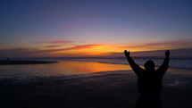 Man with his hands raised in praise and worship to God standing on a beach looking out at the ocean at sunset