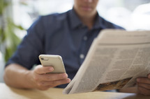 a man reading a newspaper and looking at his cellphone